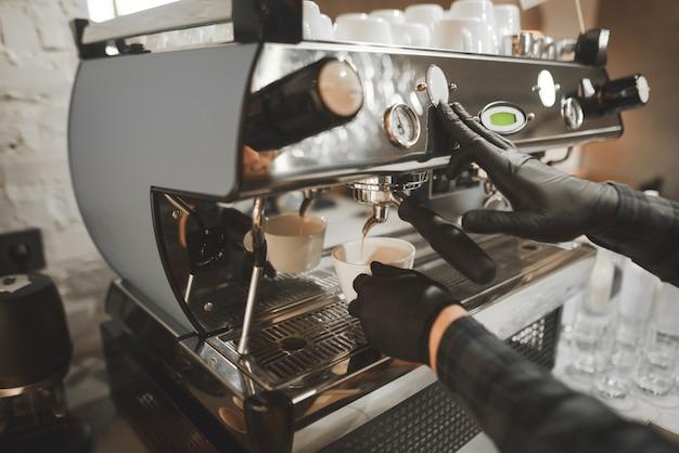 Kaffee wird aus der kaffeemaschine in eine tasse gegossen.