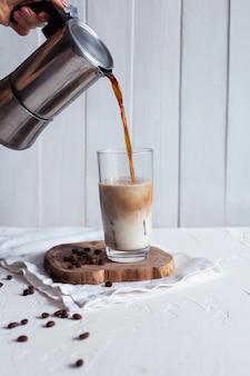 Kaffee wird mit milch in ein glas gegossen