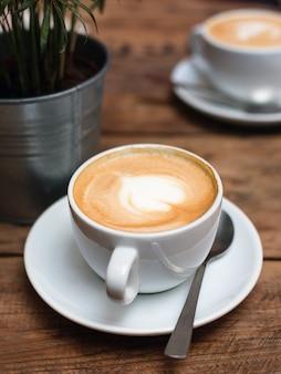 Kaffee zum frühstück. cafékultur, zwei kleine tassen cappuccino mit bild, draufsicht