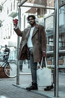 Kaffee zum mitnehmen. erfreuter bärtiger mann, der einkaufstasche in der linken hand hält und musik hört