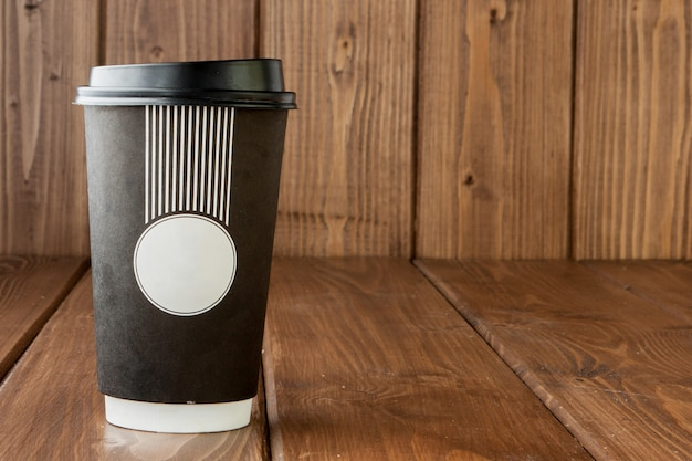 Kaffee zum mitnehmen in der thermoschale auf einem hölzernen hintergrund