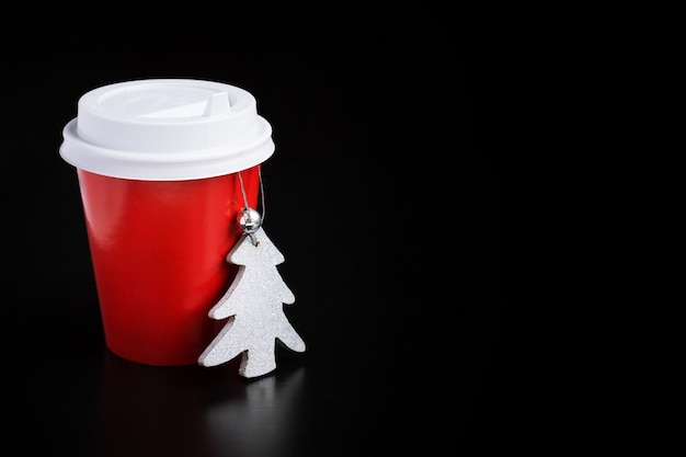 Kaffee zum mitnehmen in roten cup- und weihnachtsdekorationen auf schwarzem