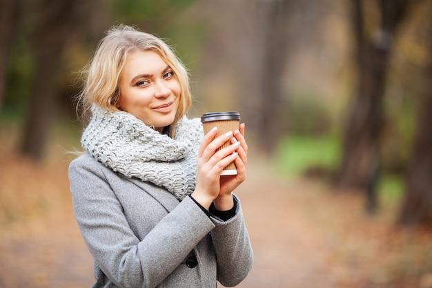 Kaffee zum mitnehmen. junge frau mit kaffee im herbstpark