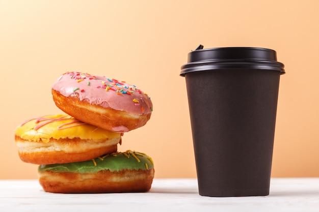 Kaffee zum mitnehmen und donuts, ein schneller snack auf dem weg. konzept des servierens des mitnehmerlebensmittels für eine kaffeestube oder eine bäckerei