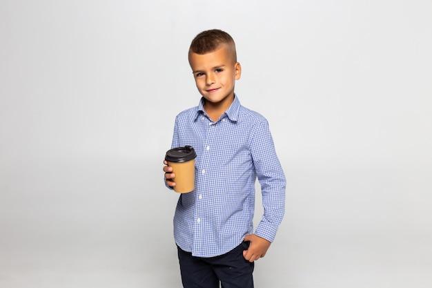 Kaffeebecher des kleinen jungen, der lokalisiert auf weißer wand steht