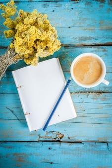Kaffeebecher mit einem strauß getrockneter wildblumen
