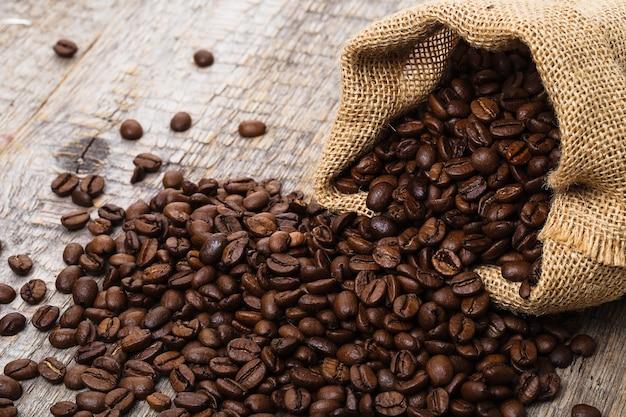 Kaffeebeutel auf altem holztisch und beutel mit kaffeebohnen