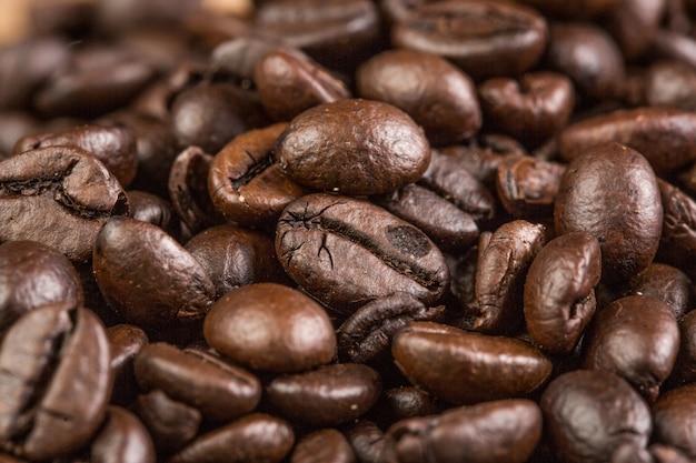 Kaffeebohne auf hölzernem hintergrund des schmutzes