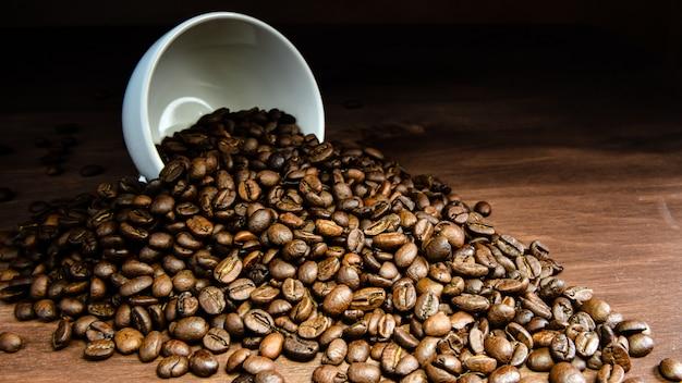 Kaffeebohne, die aus einem weißen becher auf holztisch gießt