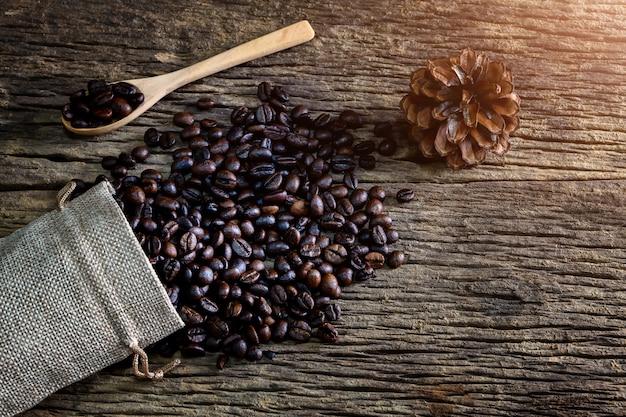 Kaffeebohne im löffel und in der tasche auf hölzernem hintergrund