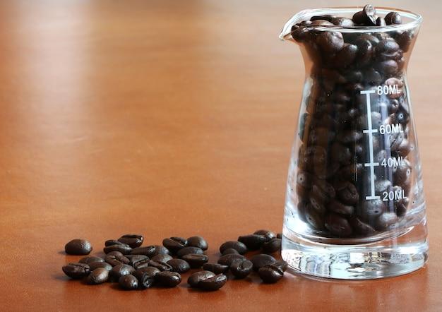 Kaffeebohne im messbecher auf dem holztisch