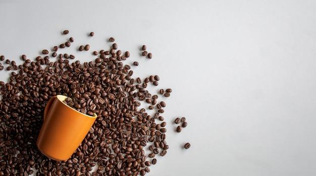Kaffeebohne in der tasse auf weißem tischhintergrund. draufsicht. platz für text