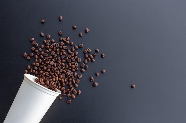 Kaffeebohne in der weißen heißen schale auf schreibtischhintergrund