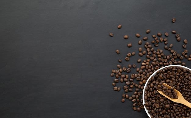 Kaffeebohne in der weißen tasse auf schwarzem holzboden. platz für text
