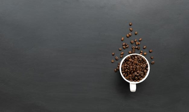 Kaffeebohne in der weißen tasse auf schwarzem holzbodenhintergrund. draufsicht. platz für text