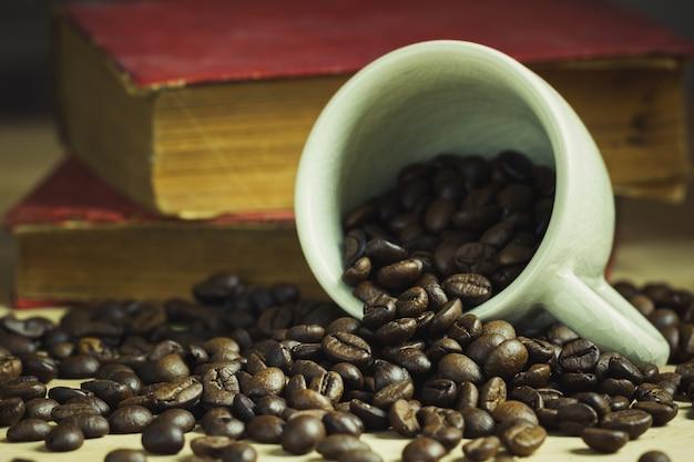 Kaffeebohne in gekippter keramischer schale und in altem buch hinter gelegt auf holztisch mit morgenlicht.