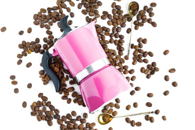 Kaffeebohne, rosa kaffeekanne und löffel auf weißem hintergrund