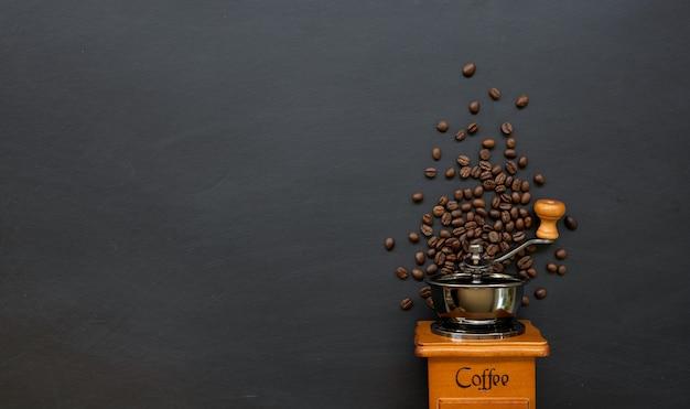 Kaffeebohne und handmühle auf schwarzem tisch. platz für text.