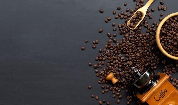 Kaffeebohne und handmühle auf schwarzem tischhintergrund. platz für text. draufsicht
