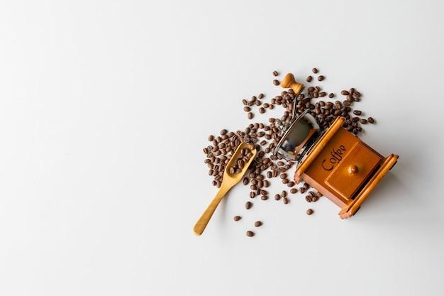 Kaffeebohne und handmühle auf weißem tischhintergrund. platz für text. draufsicht