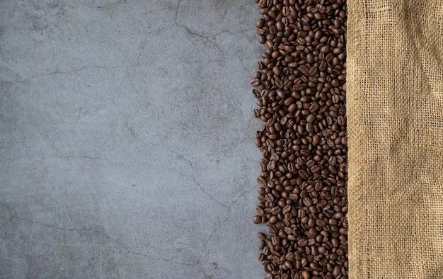 Kaffeebohne und sack auf altem zementhintergrund