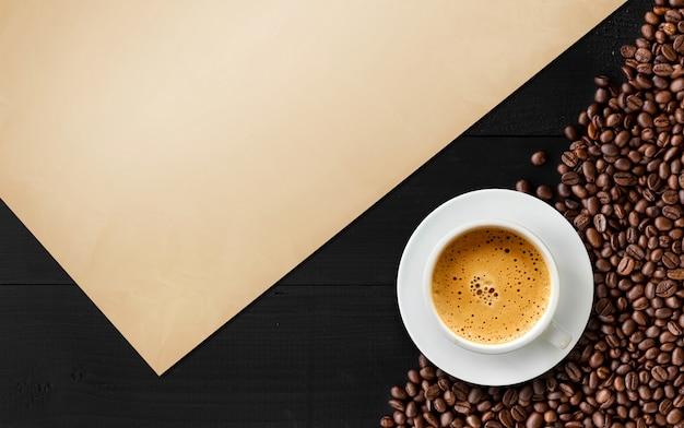 Kaffeebohne und weinlesepapier auf schwarzer hölzerner tabelle