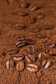 Kaffeebohnemakro auf gemahlenem kaffeehintergrund