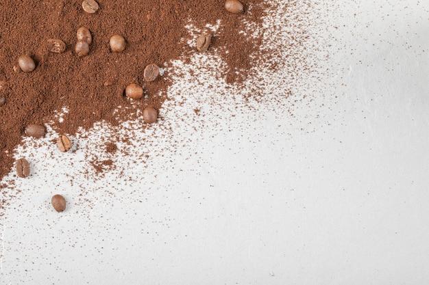 Kaffeebohnen auf dem gemischten kaffee oder kakaopulver.