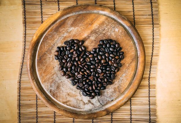 Kaffeebohnen auf dem hölzernen schneidebrett im formherz