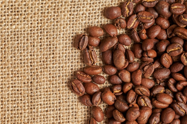 Kaffeebohnen auf dem strickmaterial für kopierraum. draufsicht.