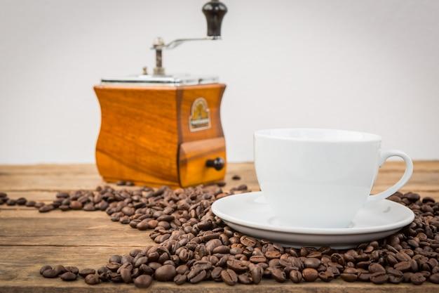 Kaffeebohnen auf einem holztisch mit einer tasse und einer mühle