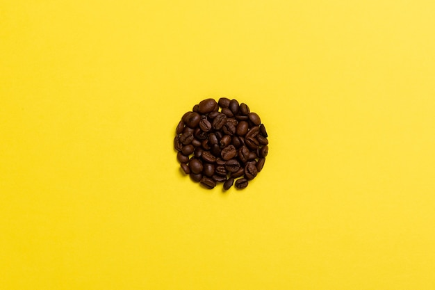 Kaffeebohnen auf einer gelben oberfläche