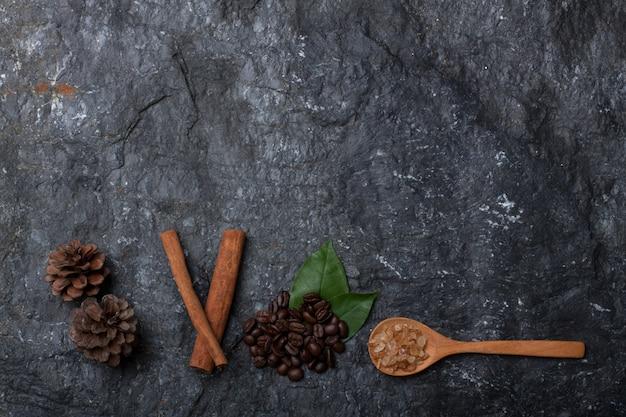 Kaffeebohnen auf grünem blatt, kiefer und zucker auf holzlöffel auf schwarzem steinhintergrund