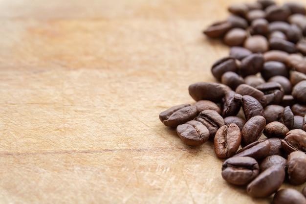 Kaffeebohnen auf hölzernem hintergrund des braunen schmutzes. nahaufnahme, vorgewählter fokus, copyspace