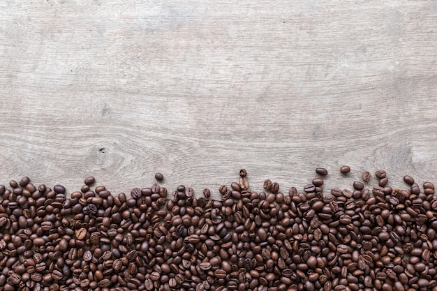 Kaffeebohnen auf holzbodenhintergrund. draufsicht