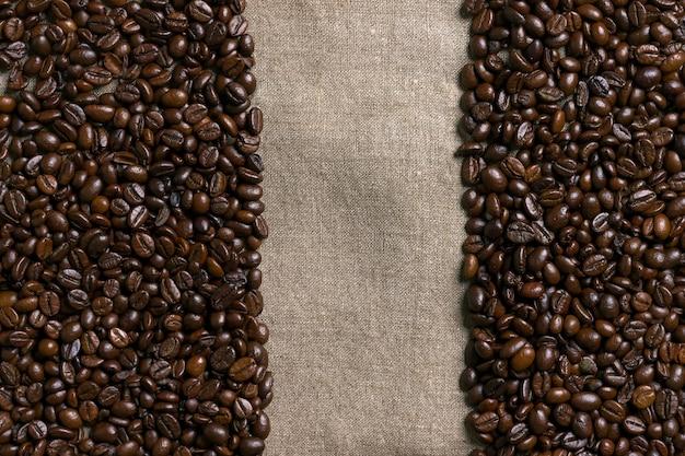 Kaffeebohnen auf leinwandhintergrund. ansicht von oben. platz kopieren. stillleben. attrappe, lehrmodell, simulation. flach legen