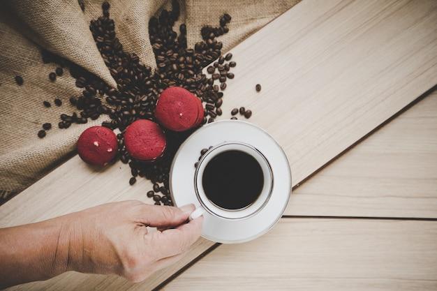 Kaffeebohnen auf leinwandsack mit kaffeejungem und rotem macaron auf hölzernem hintergrund, draufsicht.
