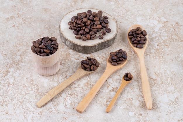 Kaffeebohnen auf löffeln, ein stück holz und eine kleine tasse