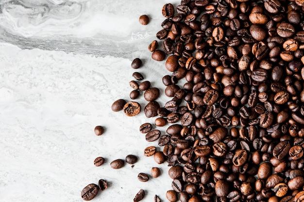 Kaffeebohnen auf marmorhintergrund mit kopienraum für text. kaffeehintergrund oder texturkonzept.