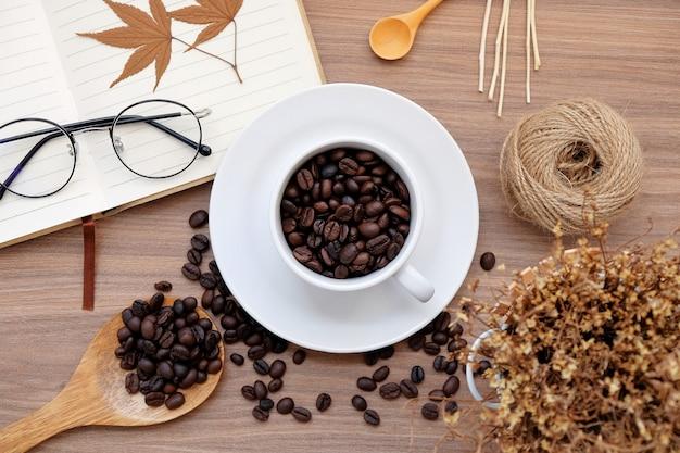 Kaffeebohnen auf schreibtisch mit herbstkonzept