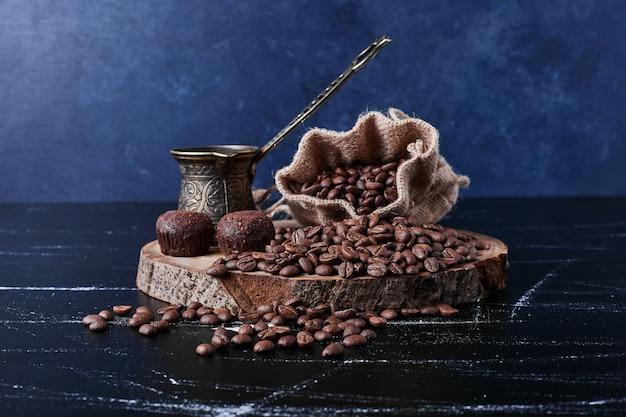 Kaffeebohnen auf schwarzem hintergrund im rustikalen paket.