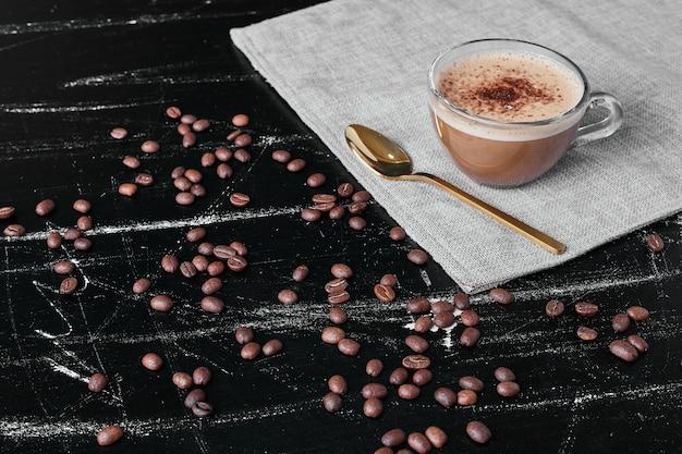 Kaffeebohnen auf schwarzem hintergrund mit getränk.