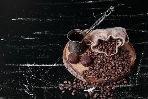 Kaffeebohnen auf schwarzem hintergrund mit pralinen.