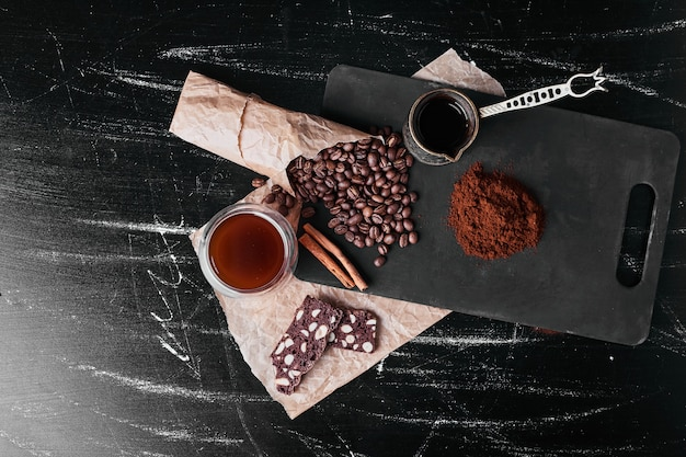 Kaffeebohnen auf schwarzem hintergrund mit pulver.