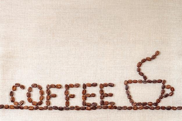 Kaffeebohnen auf stoffhintergrund.