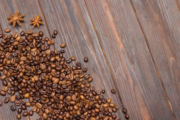 Kaffeebohnen auf tisch und sternanis verstreut.