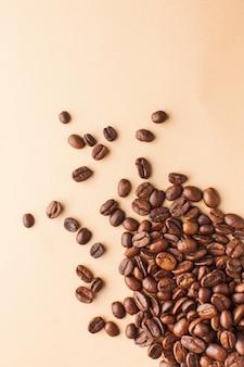 Kaffeebohnen aus der nähe sind in der unteren ecke auf hellbraunem hintergrund verteilt. vertikales foto mit platz für text. für röster, kaffeehäuser und cafés.