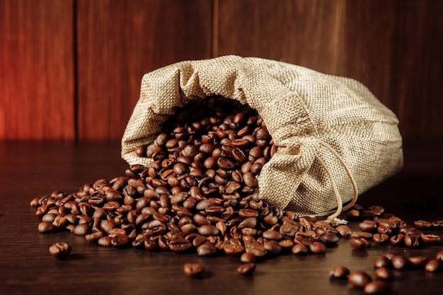 Kaffeebohnen aus der tüte auf dem tisch verstreut