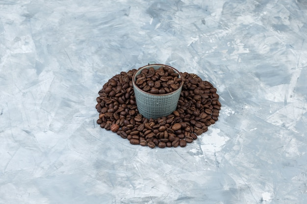 Kaffeebohnen der hohen winkelansicht in der tasse auf grauem gipshintergrund. horizontal