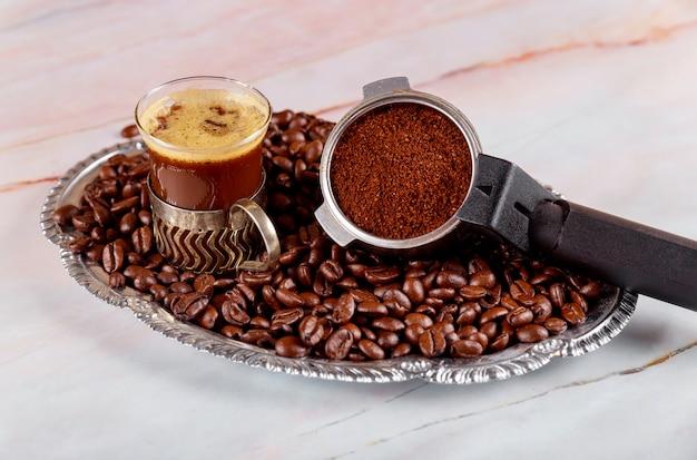 Kaffeebohnen des schwarzen espressokaffees und des siebträgers der schale